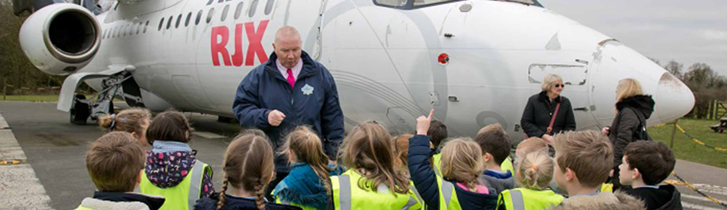 Man teaching children next to plane